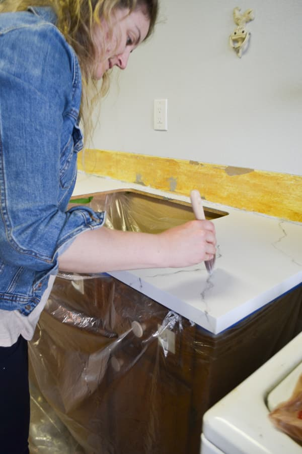 A woman wearing a jean jacket using a paintbrush to stipple grey lines on a white countertop
