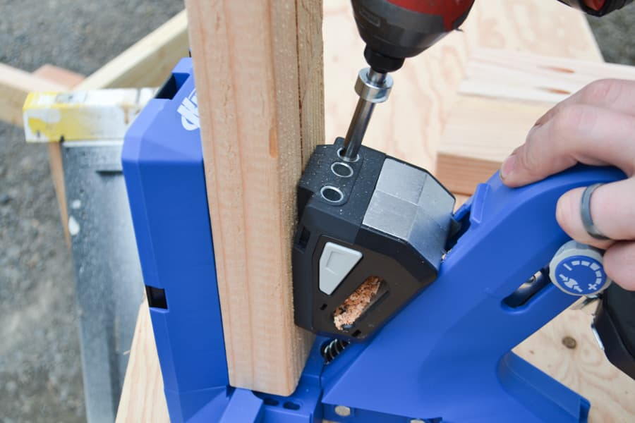 A close up of a drill being used in a wood jig to create pocket holes