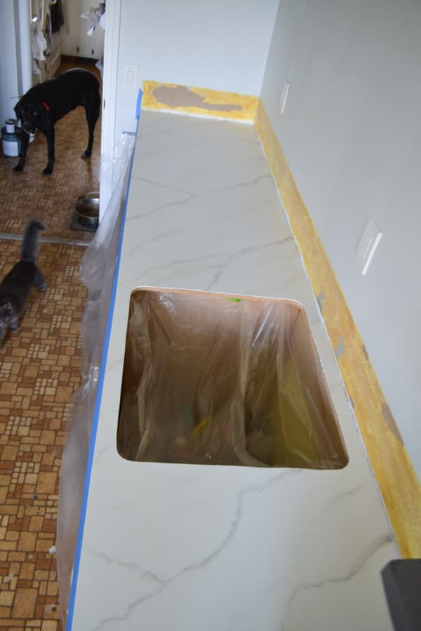 An above view of a countertop with a sink hole painted white with grey veining