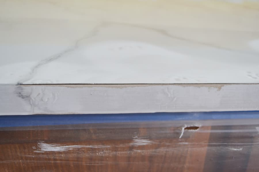 A close up of the edge of a faux marble countertop with the edge of the laminate countertop showing