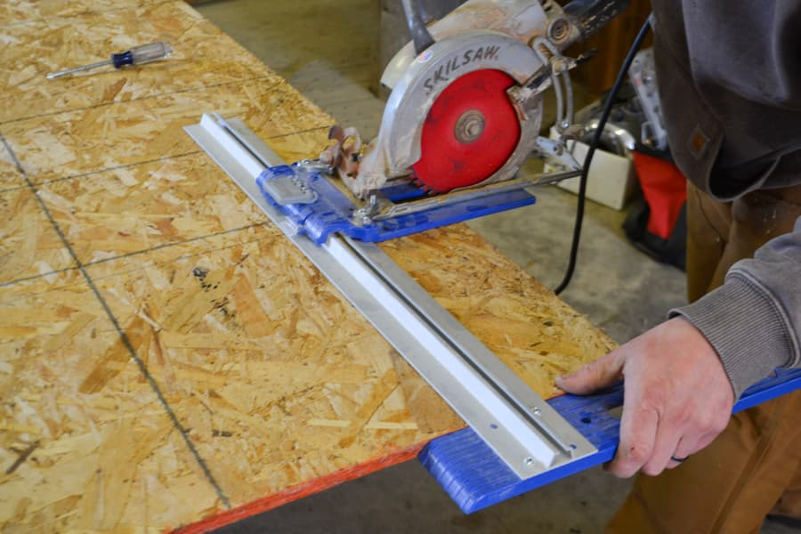 A Rip-cut jig being used to cut a piece of plywood with a skil saw