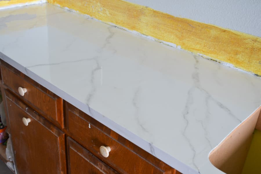 A close up of painted marble looking counterops on a brown countertop with a yellow unfinished backsplash