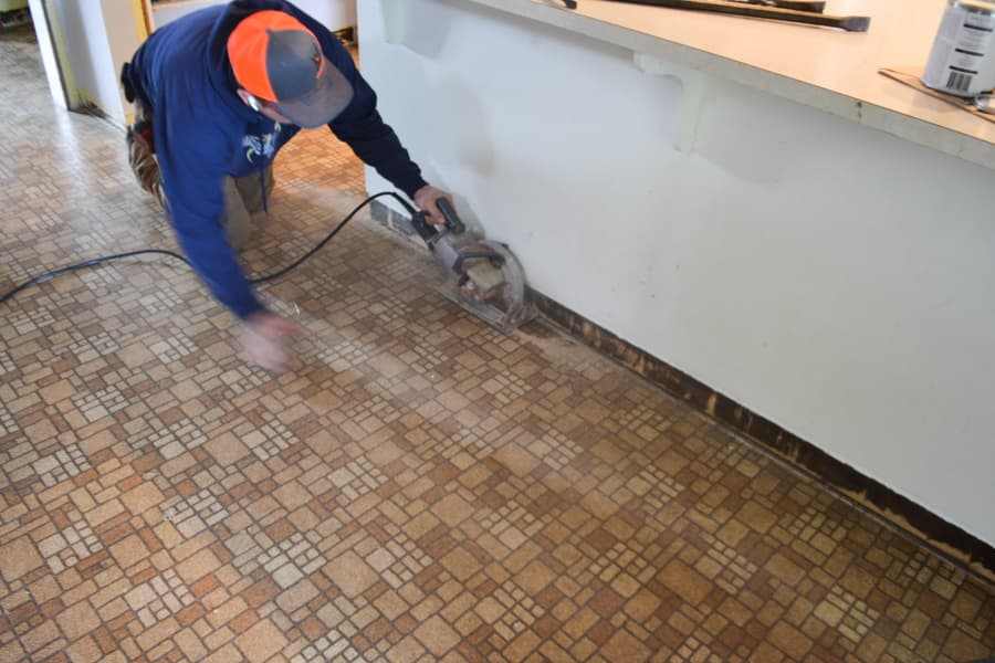 A man using a skil-saw with a cord cutting into brown tiled linoleum against a white island