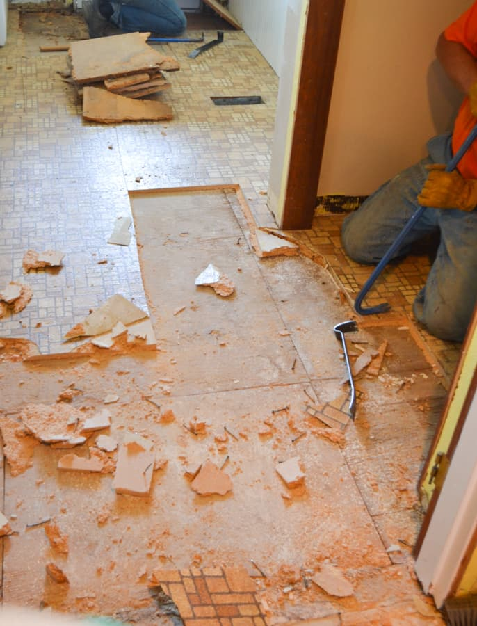 A close up of a brown tiled linoleum floor being removed in chunks