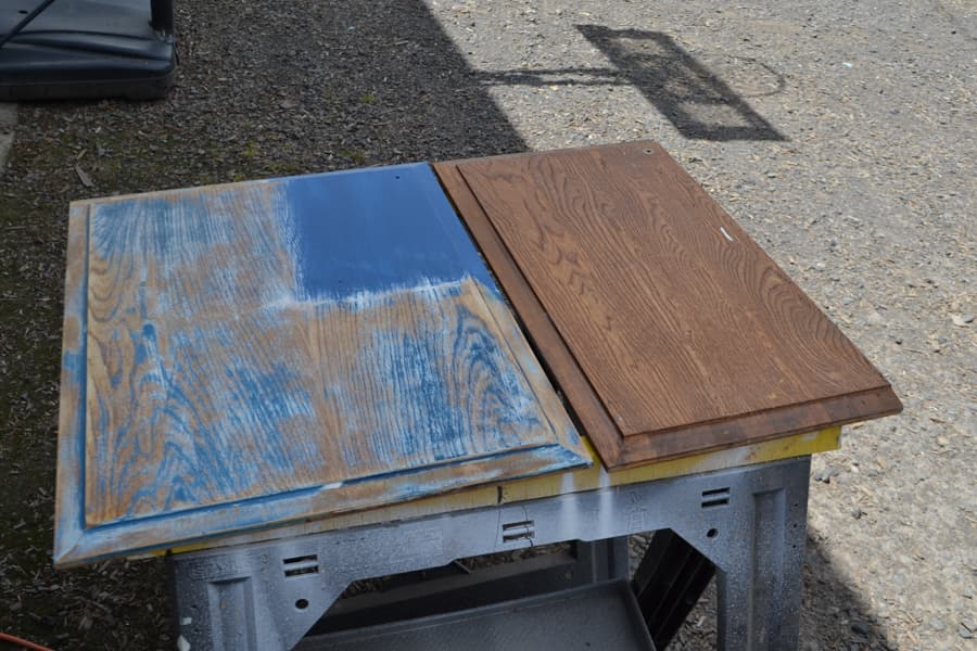 Two cabinet front sitting on sawhorses, one is brown and the other has some blue paint