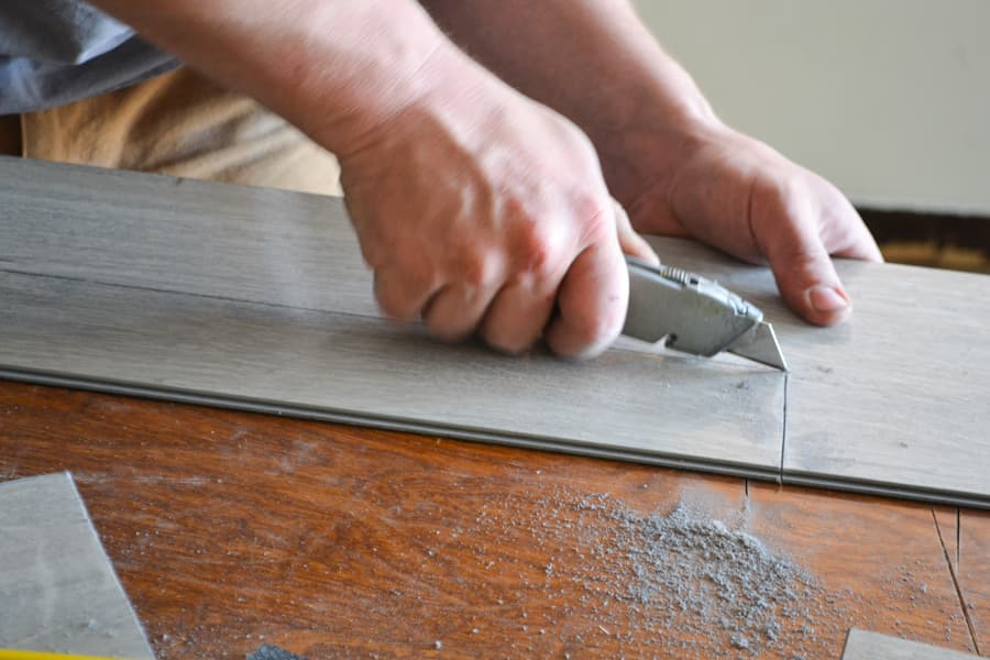 A close up of a mans hand using a box knife to cut a section of vinyl plank flooring