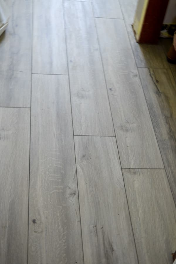 A close up of a grey plank flooring