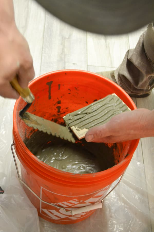 An orange bucket with gray mortar with a man's hands holding a trowel and a tile