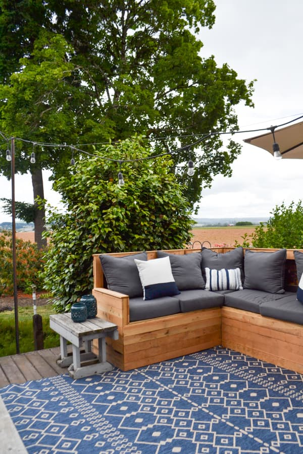 A view of the left side of a wooden sectional with dark gray cushions with a green tree and bush in the background