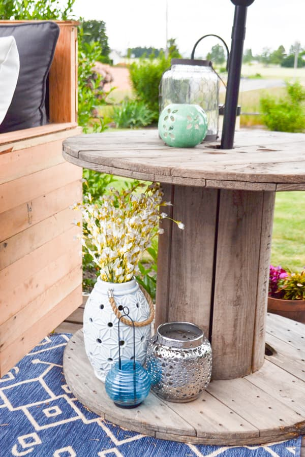 A close up of an old wire spool as an end table on an outdoor deck with lanterns underneath and on top with an umbrella sticking through the center
