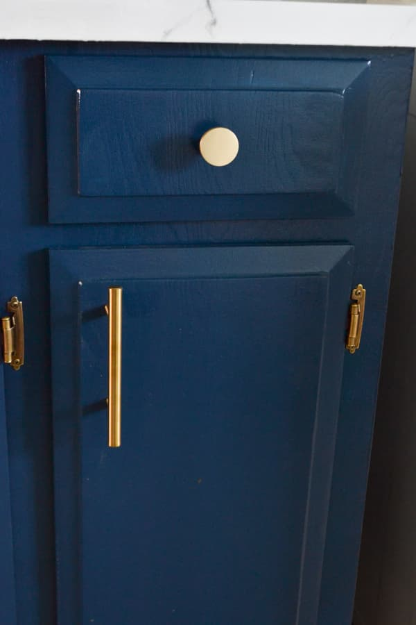 A close up of a cabinet and drawer that is painted blue and has gold hardware