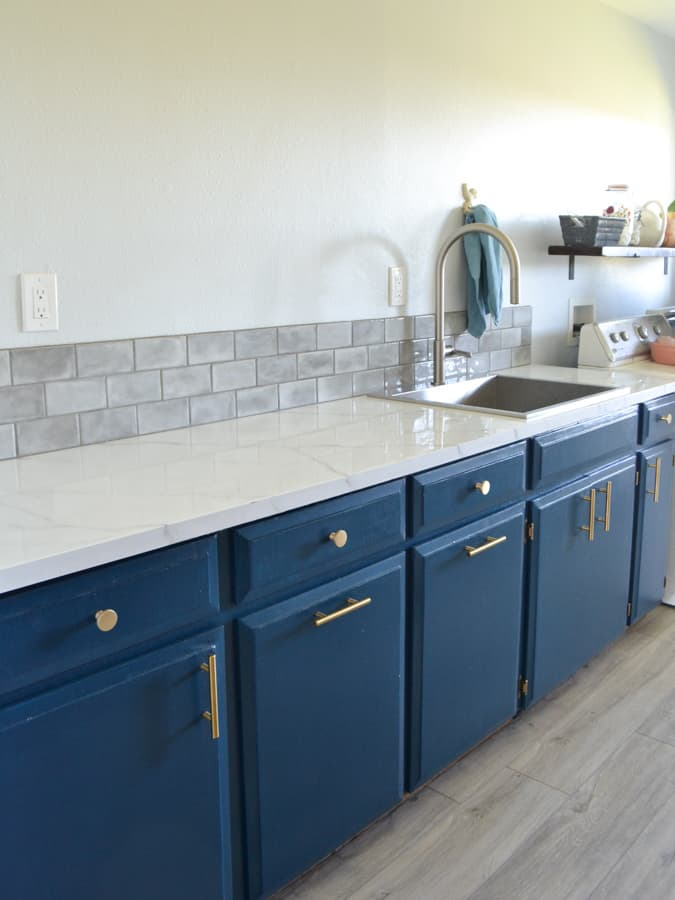 A bank of blue cabinets with gold hardware, a white marble countertop with a stainess steel sink and faucet on the left and a grey tiled backsplash