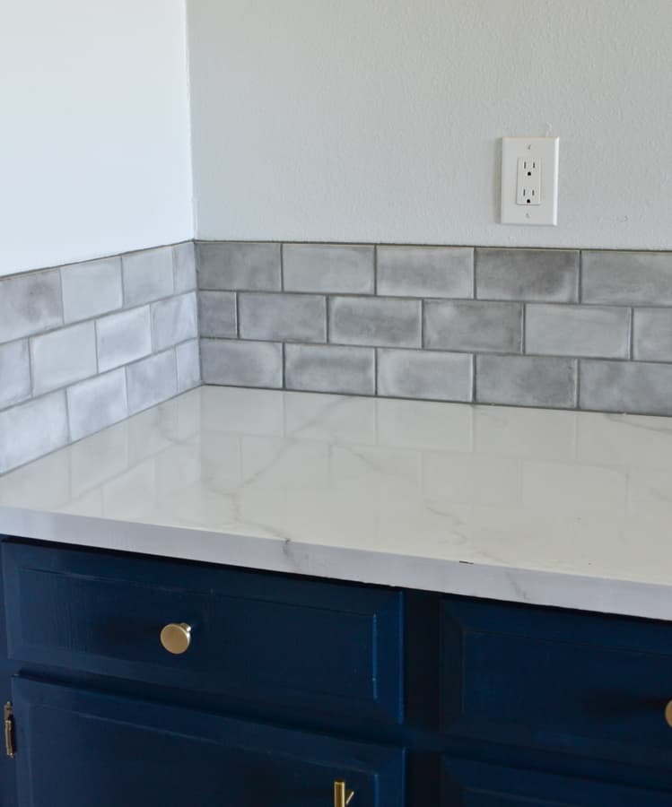 A picture of gray subway tile backsplash with a marble looking countertop and blue cabinets