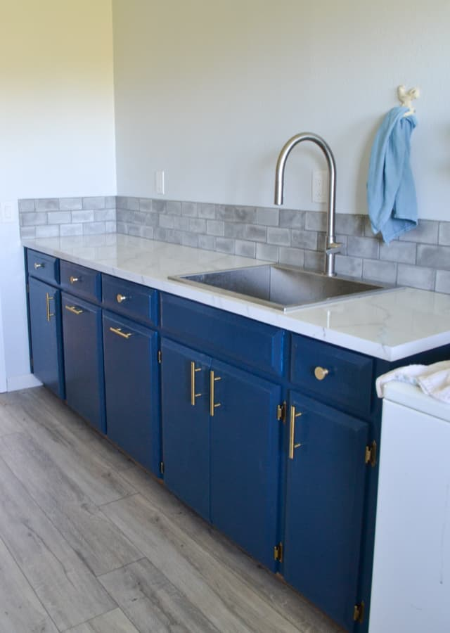 A bank of blue cabinets with gold hardware, a white marble countertop with a stainess steel sink and faucet on the right and a grey tiled backsplash