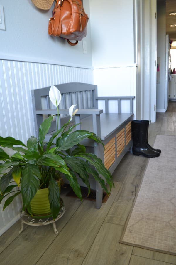 A floor view of a grey shoe storage bench with a green plant to the left and runner rug to the right