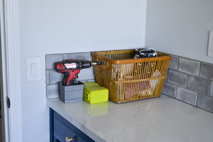 A close up of a drill and basket sitting on a laundry countertop