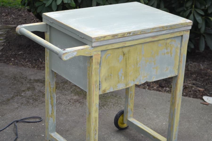 A flip top sewing table that has been sanded to expose the prior yellow paint