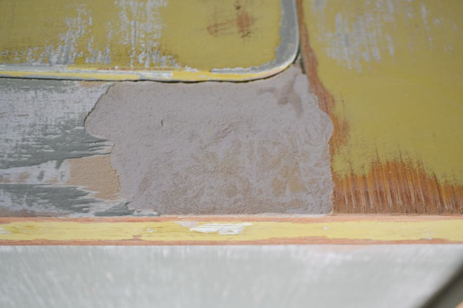 A close up of a sanded area of a wood putty spot on a yellow tabletop