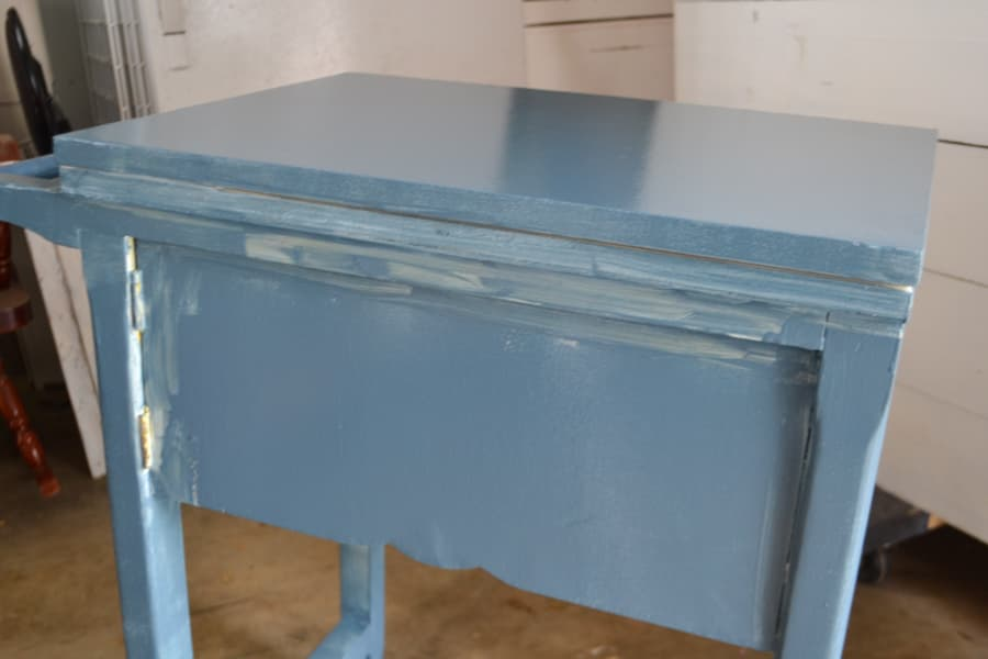A blue painted sewing table with one coat that looks a little streaky
