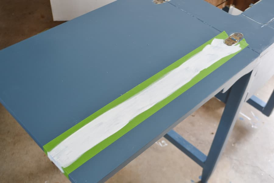 A top of a sewing table painted with a white stripe with blue background