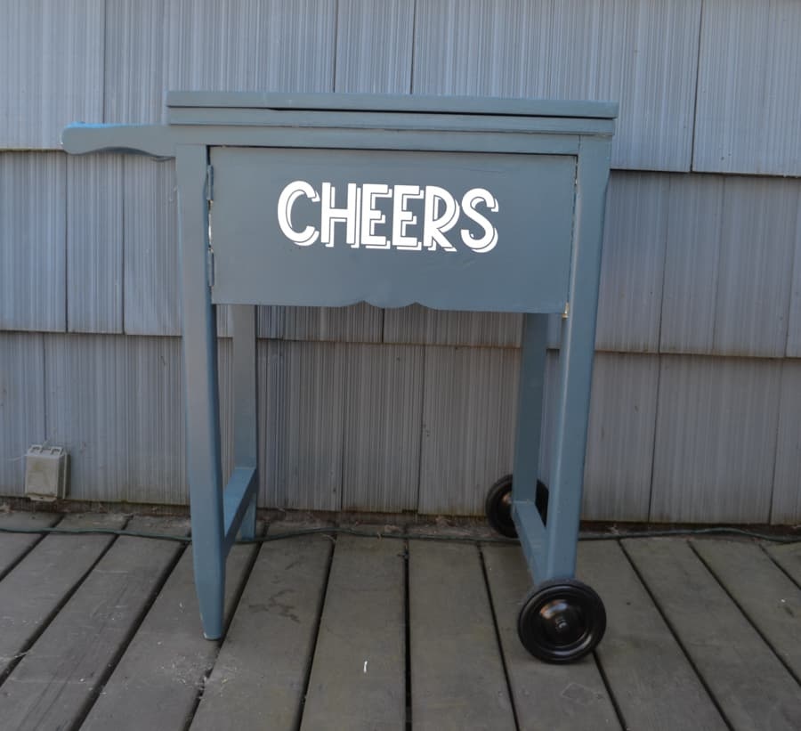 """A sewing table painted blue with the words """"Cheers"""" on the side, a handle on the left and wheels on the bottom right"""