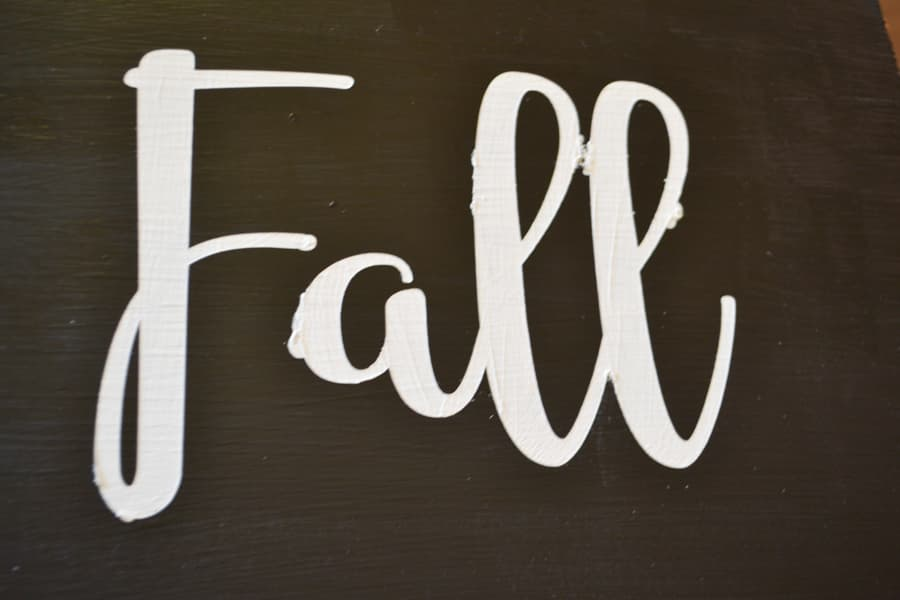 """A close up of """"Fall"""" painted wording in white with a little bit of paint that bled through"""