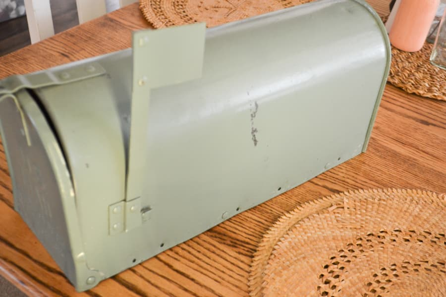 A close up of an old mailbox painted with a sage colored spray paint