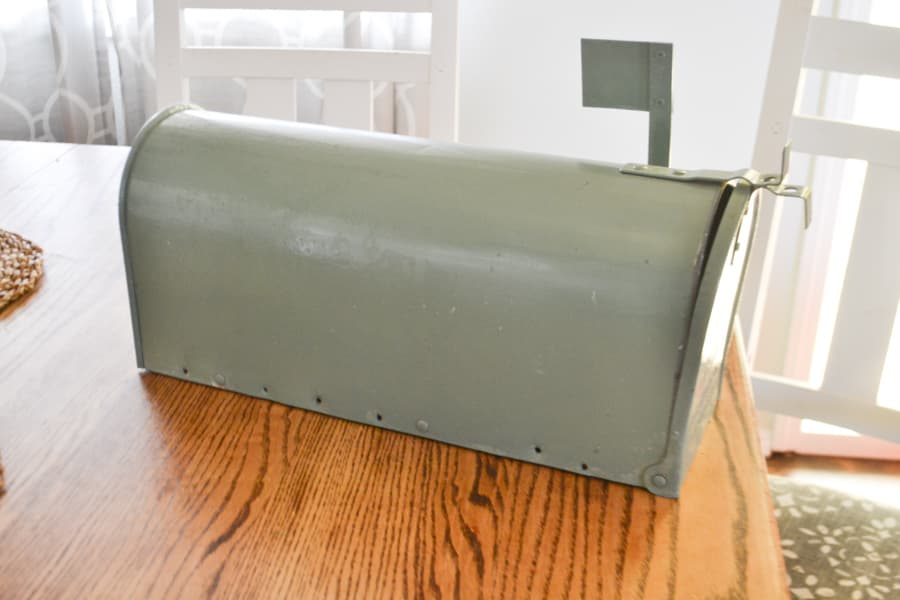 A close up of an old mailbox with the flag up that is painted a sage green color