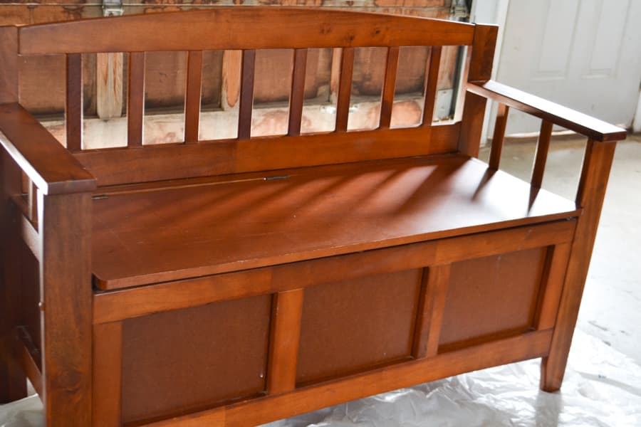 A close up of a brown shoe bench on a piece of plastic in a garage