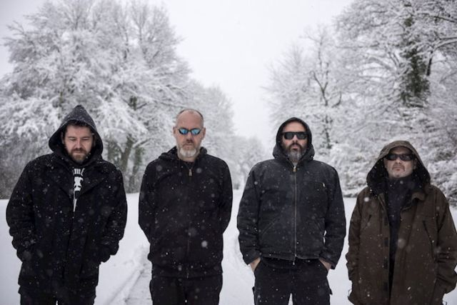 Four band members standing in the snow