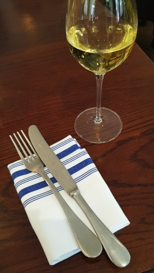 Glass of white wine and a blue-trim napkin at Clipstone London