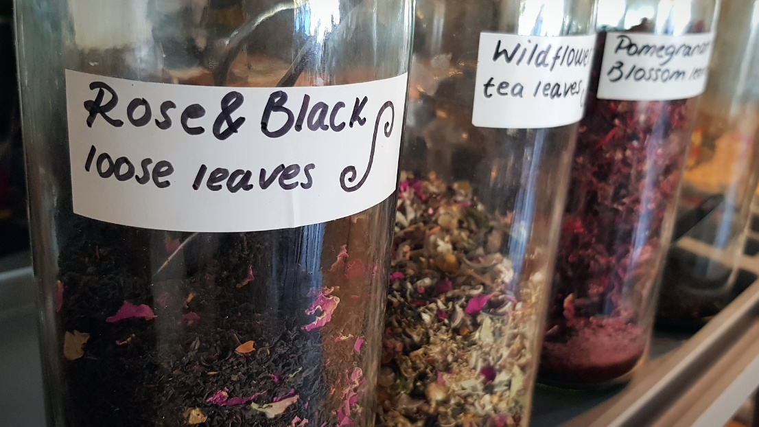 Jars of various loose leaf teas including floral and fruit teas