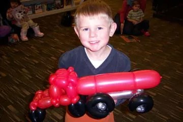 boy holding balloon animal truck