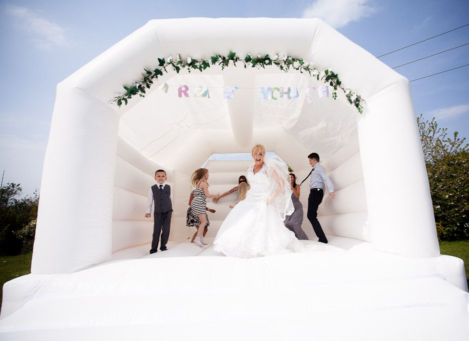 white bouncy castle on hire at a wedding