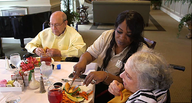 assistant helping elderly at mealtime