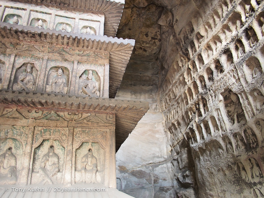A cave interior. the walls are covered with carvings and the central pillar is part of the cave itself, carved out of solid rock