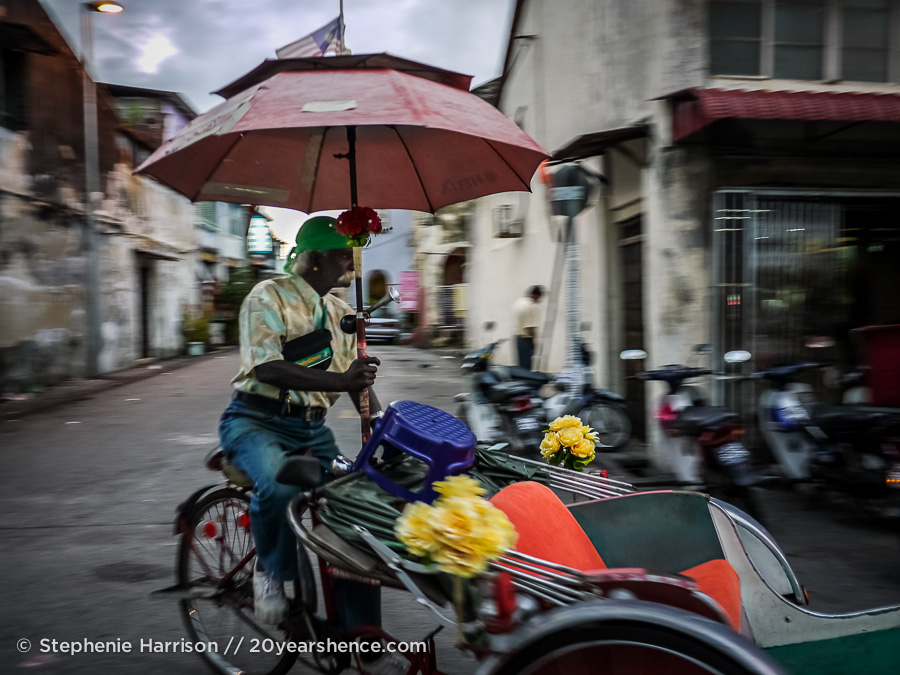 Man on a colorful trishaw in George Town, Penang
