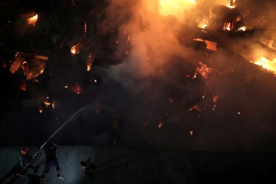 Firefighters attempt to extinguish a fire that broke out at a slum in Dhaka