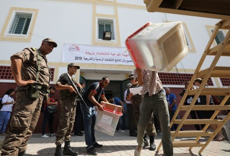 Army soldiers stand guard as polling agents transport ballot boxes and election material to be distributed to polling stations in Tunis