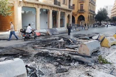 People walk through damage a day after protests targeting the government over an economic crisis in Beirut