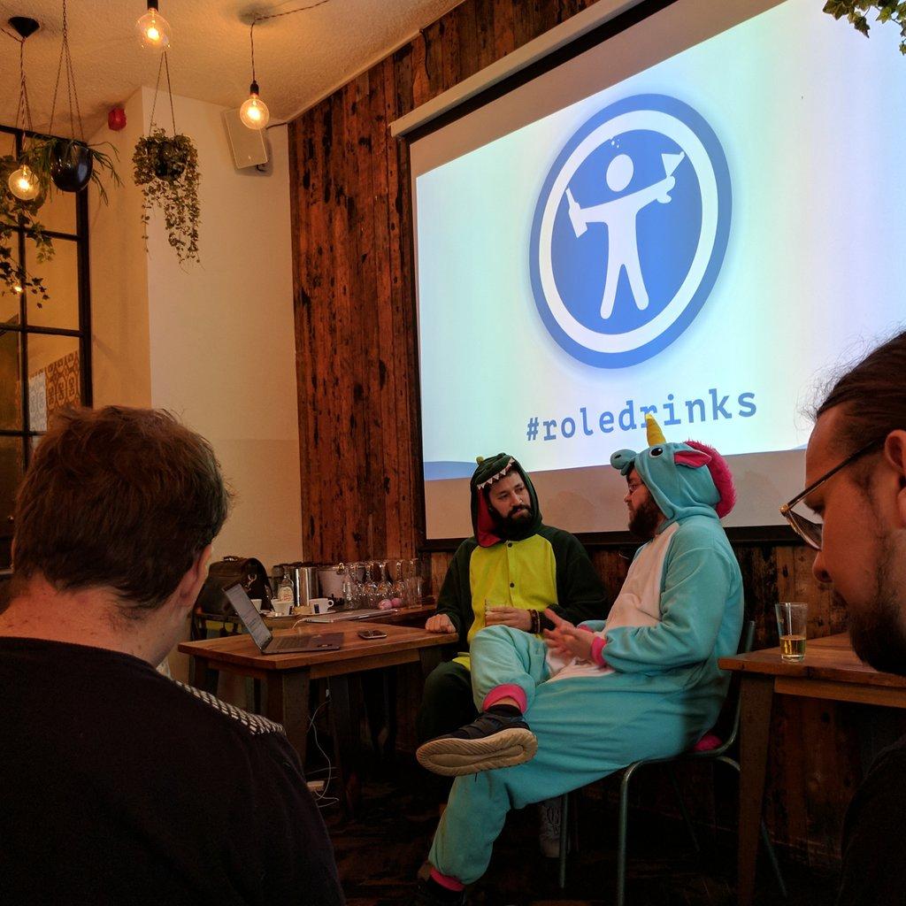 Michiel Bijl, wearing a Dinosaur Onesie, is debating Martin Splitt, who is wearing a Unicorn onesie.