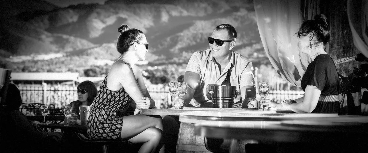 2Hawk Vineyard and Winery Friends Enjoying Wine-Tasting Against Stunning Mountain Backdrop (Grayscale)