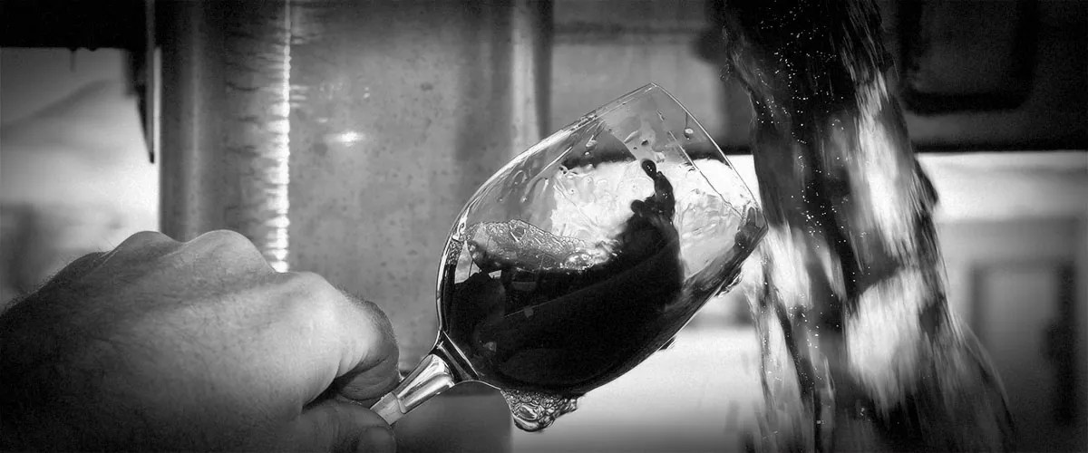 2Hawk Vineyard and Winery Winemaker Kiley Evans Testing Red Wine with Wine Glass (Grayscale)