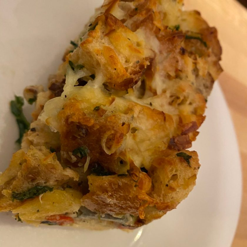 A slice of savoury bread pudding waiting to be eaten