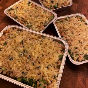 Four foil pans filled with homemade macaroni and cheese with sneaky vegetables