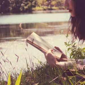 Woman reading a paperback book by a body of water