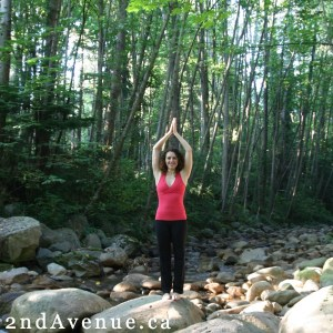 A woman in a red tank top with arms above her head and palms together in a yoga-like posture