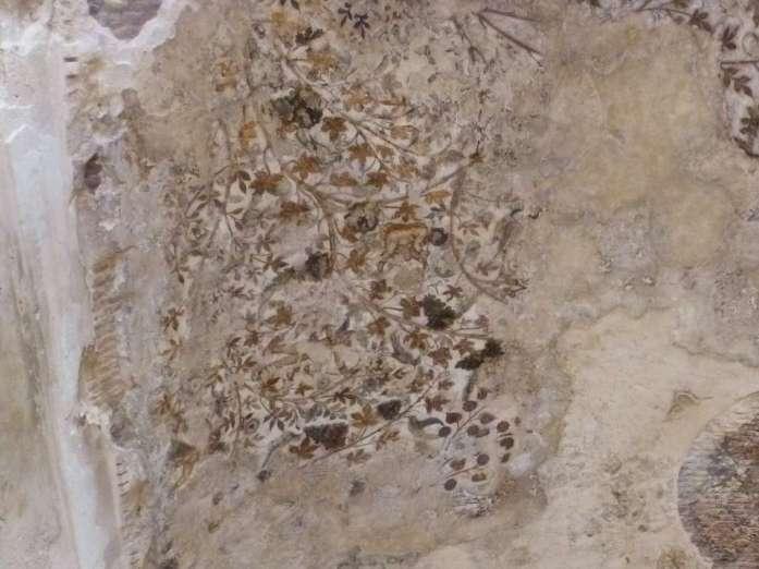 Mit Blüten bemalte Felsdecke in einer Höhle in Little Petra