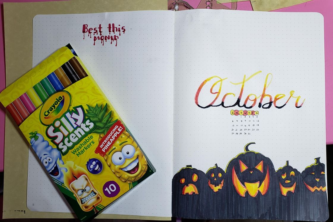 An October bullet journal monthly cover page featuring the month's name: October in yellow, orange and black calligraphy writing. Below, several pumpkins drawn and colored with black, with the carved faces shaded to look as if they are lit from within. A pack of Crayola silly scents lays on the opposite page.
