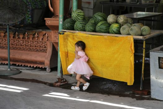Local kids play amongst fruit stalls as their parents work